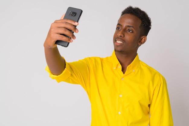 Retrato de um jovem africano com cabelo afro, vestindo uma camisa amarela contra uma parede branca