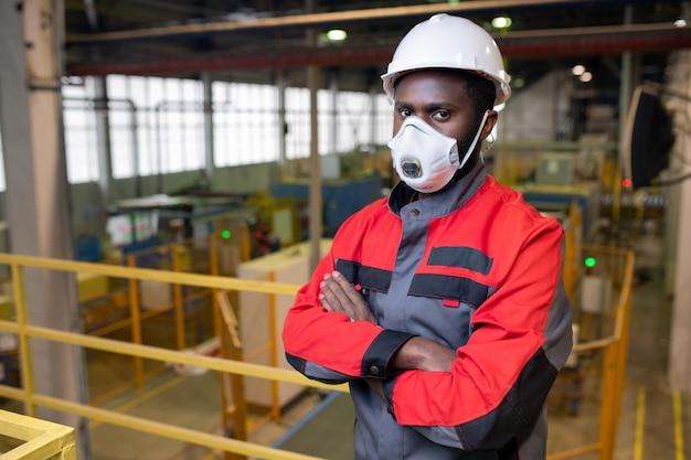 Retrato de um jovem africano confiante com respirador e capacete trabalhando na indústria de produtos tóxicos