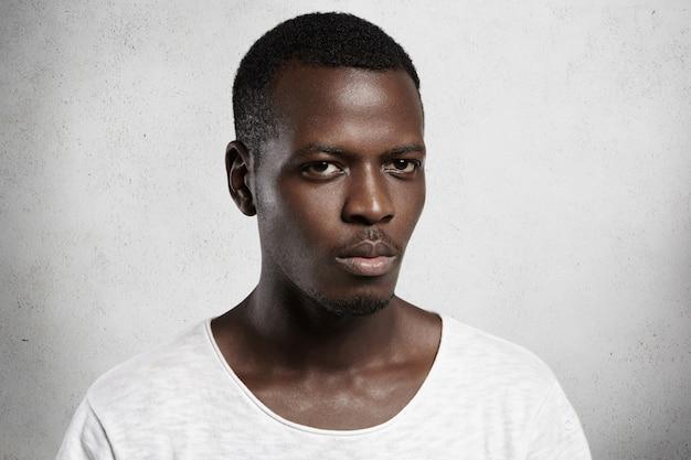 Retrato de um jovem africano confiante e bonito vestido casualmente com expressão facial séria ou com raiva.