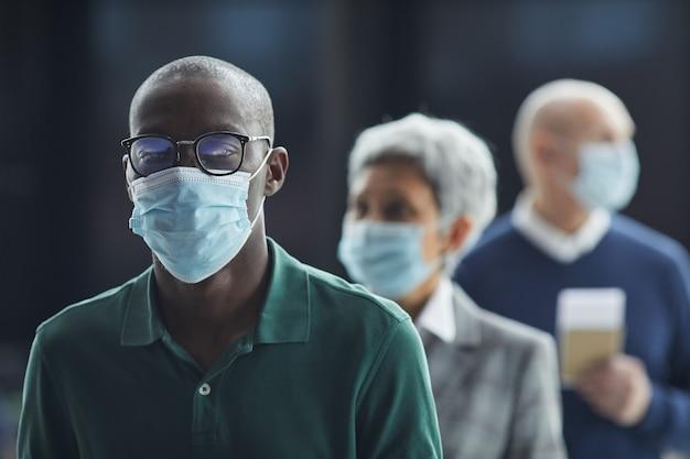 Retrato de um jovem africano de óculos e máscara protetora, olhando em pé em uma fila