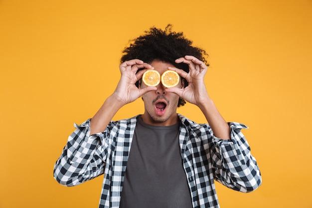 Retrato de um jovem africano engraçado segurando laranja fatiada