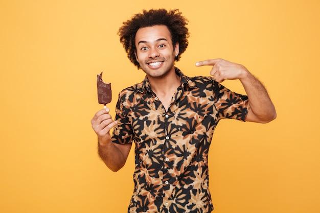 Retrato de um jovem africano feliz comendo sorvete