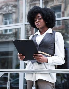 Retrato, de, um, jovem, africano, mulher negócios fica, frente, trilhos, segurando clipboard