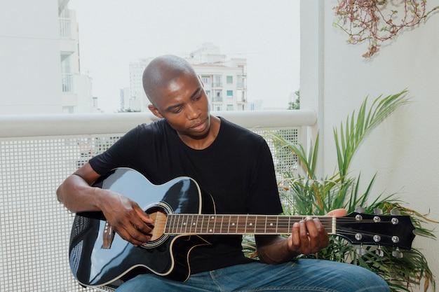 Retrato de um jovem africano sentado na varanda tocando violão