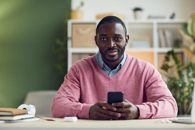 Retrato de um jovem africano sorrindo para a câmera enquanto está sentado à mesa e usando seu telefone celular