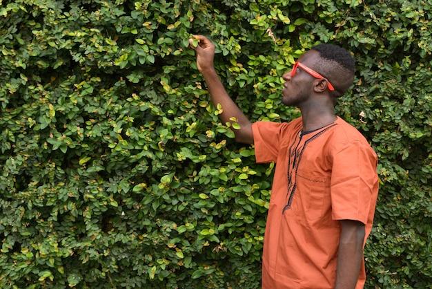 Retrato de um jovem africano vestindo roupas tradicionais contra uma sebe verde ao ar livre