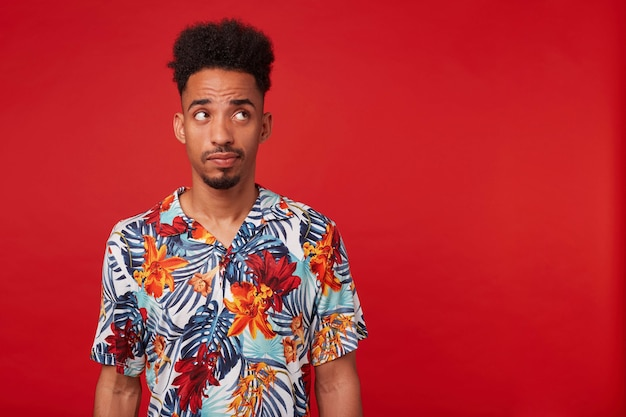Retrato de um jovem afro-americano a pensar, usa uma camisa havaiana, olhando para a direita na copyspace, em pé sobre um fundo vermelho.