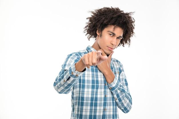 Retrato de um jovem afro-americano apontando o dedo isolado em uma parede branca