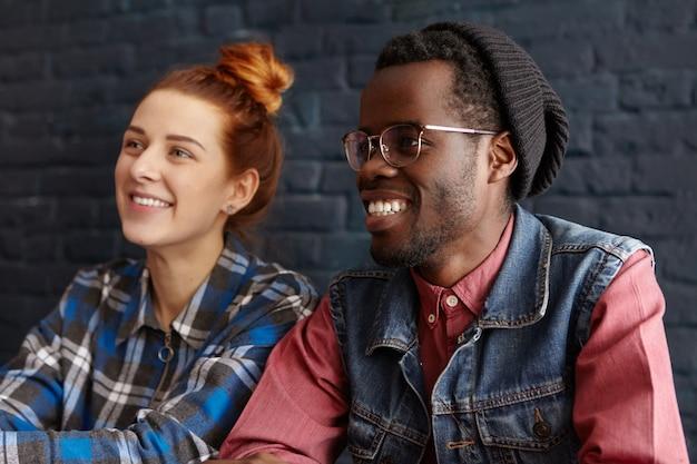 Retrato de um jovem afro-americano bonito de óculos e chapéu hipster relaxando em um café com sua amiga