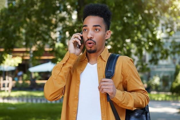 Retrato de um jovem afro-americano caminhando no parque, vestindo uma camisa amarela e uma camiseta branca, falando ao telefone com a boca bem aberta, ouve notícias incríveis, parece surpreso.