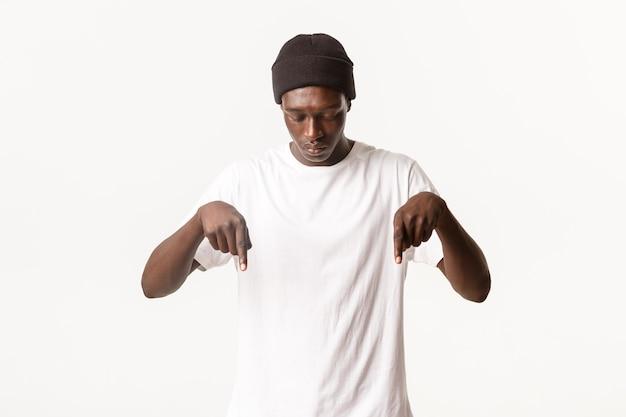 Retrato de um jovem afro-americano curioso no gorro, olhando e apontando para baixo, mostrando o logotipo