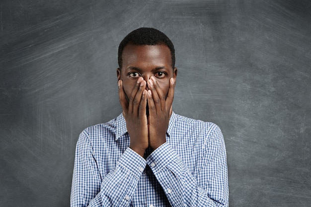 Retrato de um jovem afro-americano de camisa quadriculada cobrindo a boca com as duas mãos e olhando com uma expressão chocada e culpada como se tivesse feito algo errado, parado diante do quadro-negro