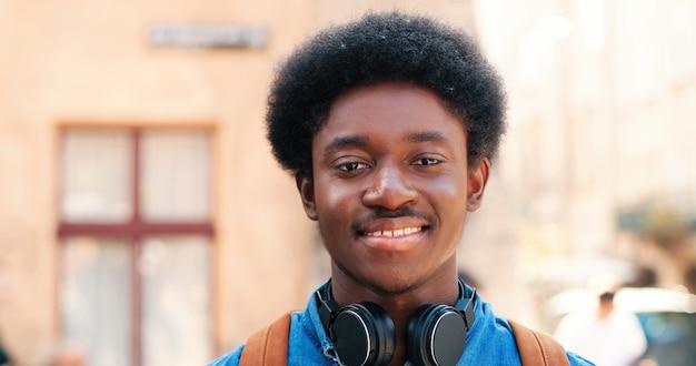 Retrato de um jovem afro-americano de etnia multirracial, com fones de ouvido em pé no aquecedor.