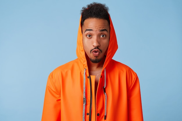 Retrato de um jovem afro-americano de pele escura espantado com capa de chuva laranja, que soube que sua banda favorita está lançando um novo álbum, maravilhado com a notícia, diz que lábios uau. stands.