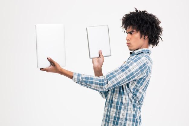 Retrato de um jovem afro-americano escolhendo entre um tablet ou um pequeno laptop isolado em uma parede branca.