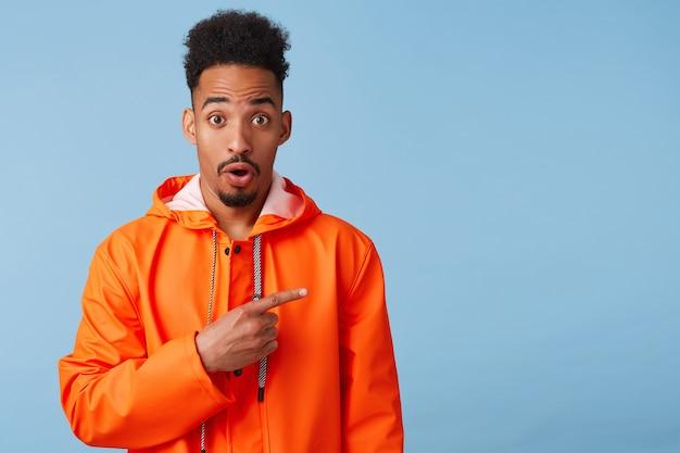 Retrato de um jovem afro-americano espantado de pele escura com uma capa de chuva laranja, quer chamar a atenção do seu dedo para a direita