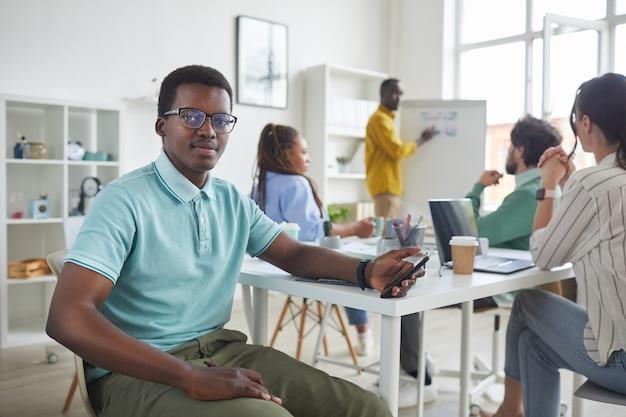 Retrato de um jovem afro-americano sentado à mesa durante uma reunião com a equipe de negócios