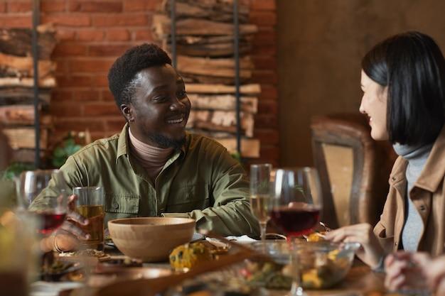 Retrato de um jovem afro-americano sorrindo para uma amiga enquanto aprecia um jantar ao ar livre
