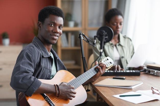 Retrato de um jovem afro-americano tocando violão e olhando para a câmera enquanto compõe uma música em um estúdio de gravação doméstico, copie o espaço