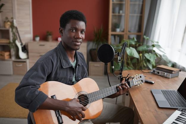 Retrato de um jovem afro-americano tocando violão e olhando para a câmera enquanto está sentado ao lado do microfone no estúdio de gravação em casa, copie o espaço