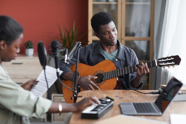 Retrato de um jovem afro-americano tocando violão enquanto compõe música em um estúdio de gravação caseiro, copie o espaço