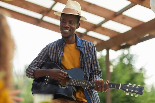Retrato de um jovem afro-americano tocando violão enquanto janta com amigos ao ar livre na festa de verão
