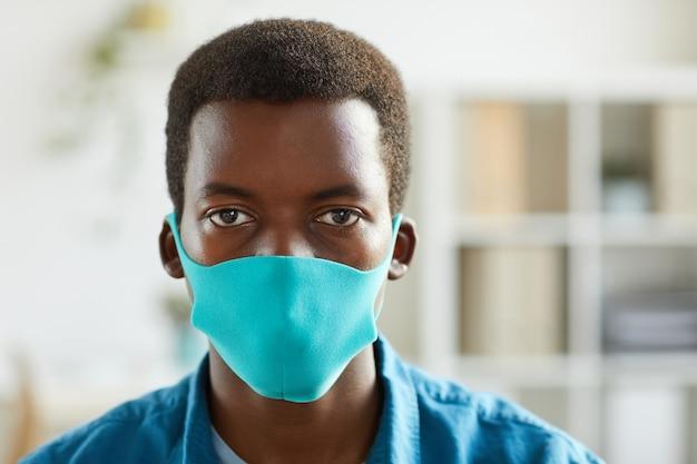 Retrato de um jovem afro-americano usando máscara e em pé no escritório pós-pandemia