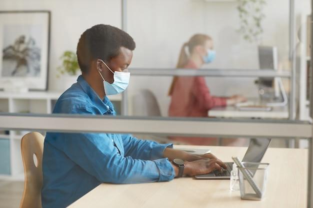 Retrato de um jovem afro-americano usando máscara e usando o laptop enquanto está sentado à mesa em um cubículo no escritório pós-pandemia