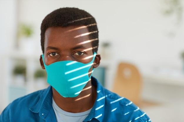 Retrato de um jovem afro-americano usando máscara facial, posando em um local de trabalho iluminado pelo sol em um escritório pós-pandêmico