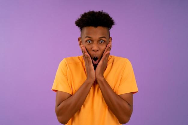 Retrato de um jovem afro com expressão chocada em pé contra um fundo isolado.