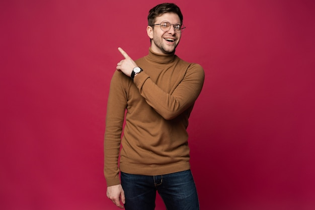 Retrato de um jovem alegre apontando os dedos para o espaço da cópia na palma da mão isolado sobre o fundo rosa.