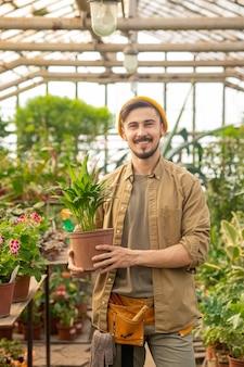 Retrato de um jovem alegre homem de efeito estufa com barba e bigode segurando um vaso de planta em uma estufa