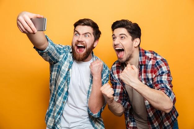 Retrato de um jovem alegre tomando um selfie