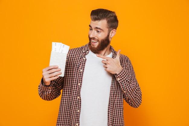 Retrato de um jovem alegre vestindo roupas casuais, mostrando passaporte com passagens aéreas