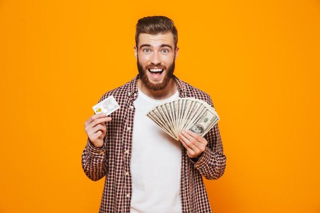 Retrato de um jovem alegre, vestindo roupas casuais, segurando notas de dinheiro e mostrando um cartão de crédito de plástico