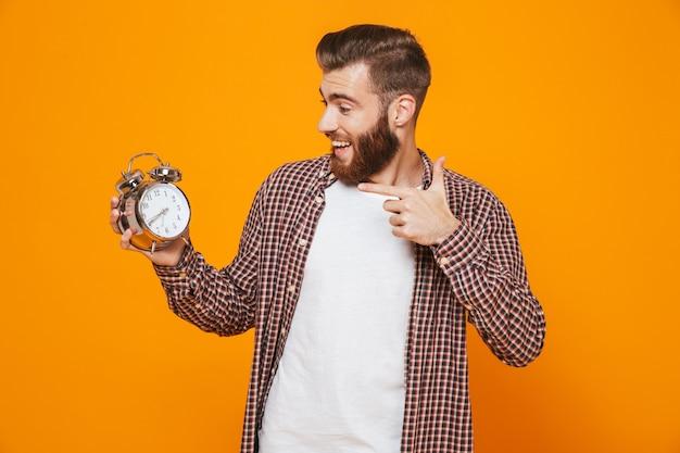 Retrato de um jovem alegre, vestindo roupas casuais, segurando um despertador mostrando os polegares para cima