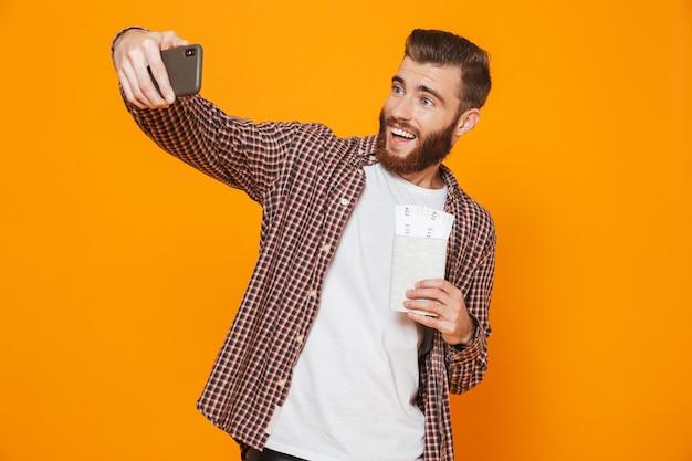 Retrato de um jovem alegre, vestindo roupas casuais, tirando uma selfie mostrando o passaporte com passagens aéreas