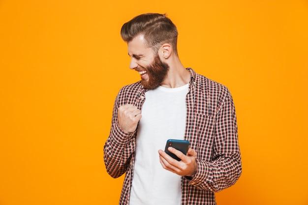 Retrato de um jovem alegre, vestindo roupas casuais, usando telefone celular