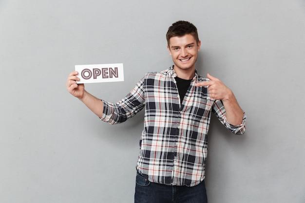 Retrato de um jovem animado apontando o dedo para uma placa aberta