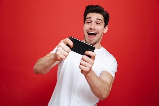 Retrato de um jovem animado em jogar t-shirt branca