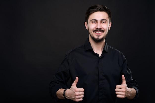 Retrato de um jovem animado em pé contra a parede preta e mostrando o polegar para cima como símbolo de qualidade