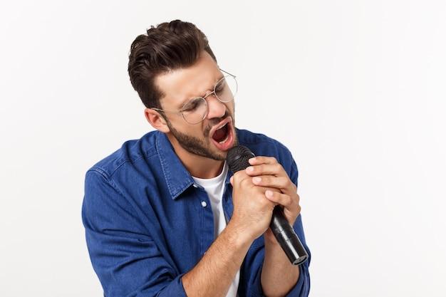 Retrato de um jovem animado em t-shirt isolado sobre fundo cinza, cantando.