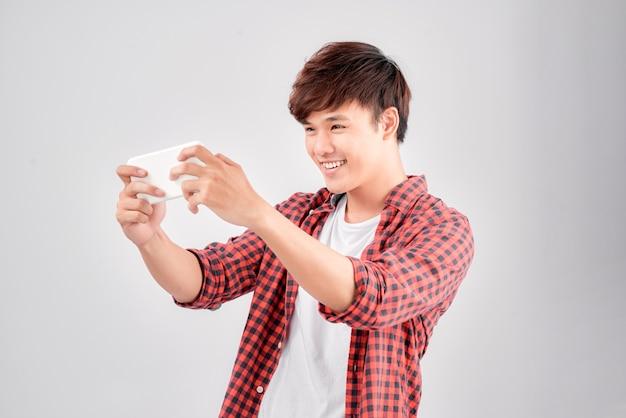 Retrato de um jovem animado jogando no celular
