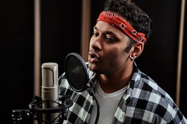 Retrato de um jovem artista de hip hop cantando em um microfone condensador enquanto grava uma música em