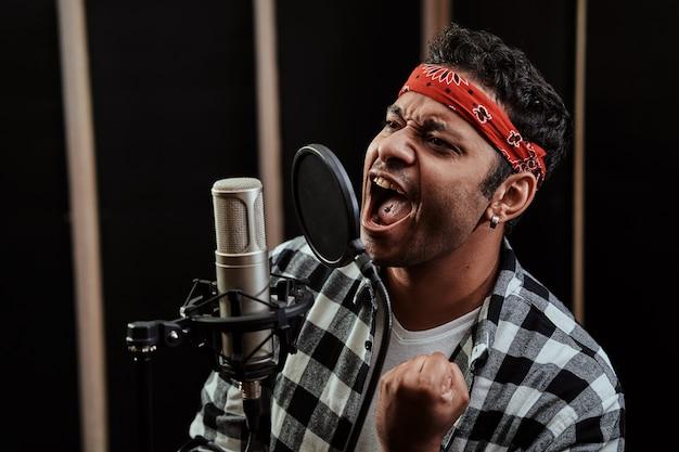 Retrato de um jovem artista de hip hop olhando focado cantando em um microfone condensador enquanto