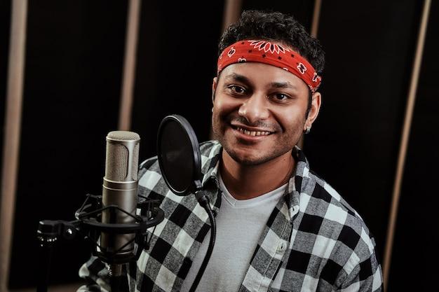 Retrato de um jovem artista de hip hop sorrindo para a câmera enquanto grava uma música em um profissional