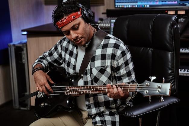 Retrato de um jovem artista masculino focado em fones de ouvido, tocando guitarra, enquanto está sentado na gravação