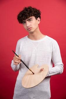 Retrato de um jovem artista masculino segurando paleta e pincéis.