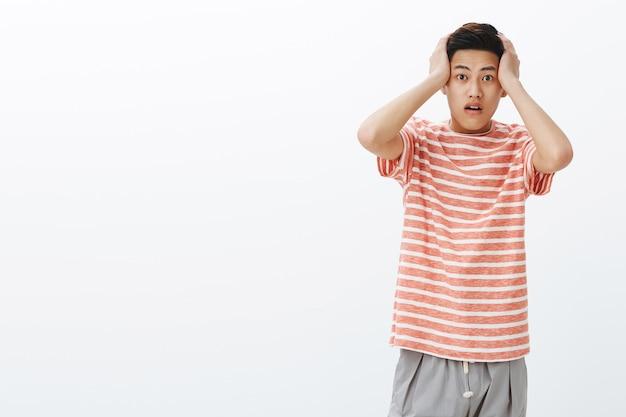 Retrato de um jovem asiático chocado em estado de estupor, pressionando as mãos na cabeça com a boca aberta de espanto, sem palavras