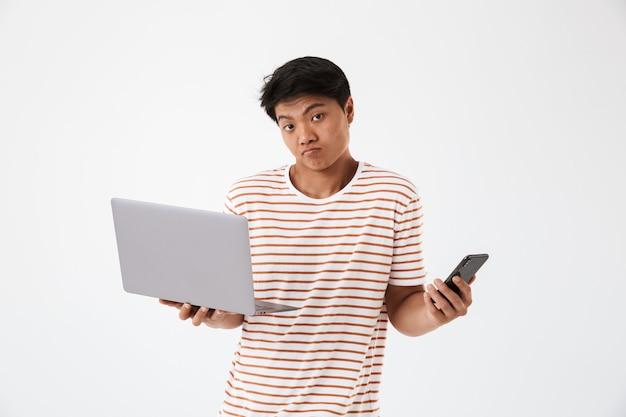 Retrato de um jovem asiático confuso a encolher os ombros